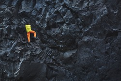 male rock climber. rock climber climbs on a rocky wall on the ocean bank. man makes hard move without rope.