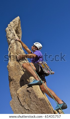Male rock climber scrambles to the summit of a sheer pinnacle.
