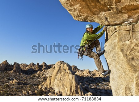 Male rock climber struggles for his next grip as he clings to a sheer cliff.