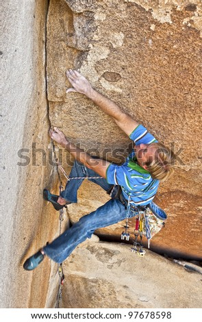 Male rock climber struggles for his next grip on a challenging ascent.