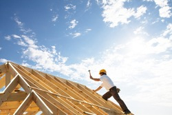 male roofer carpenter working on roof structure on construction site