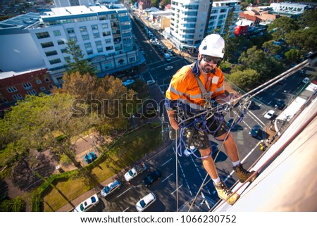 Male rope access industry worker wearing full body safety harness, white hard hat, using static twin ropes working abseiling from construction high rise building site in Sydney city, Australia