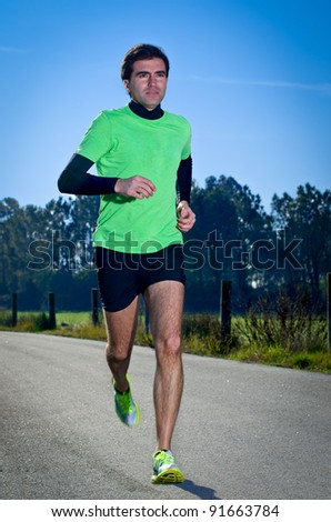 Male runner at sprinting speed training for marathon outdoors on c country landscape.