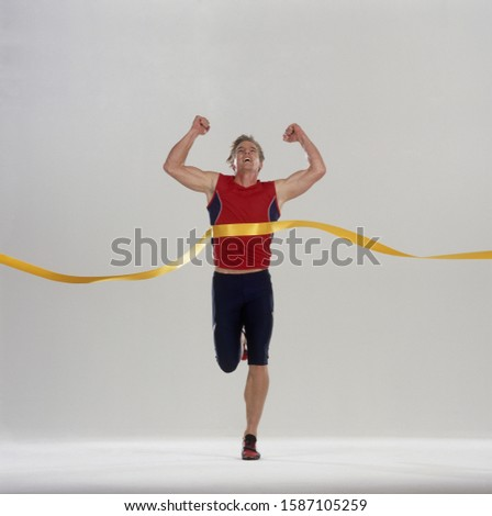 Male runner crosses finish line in triumph