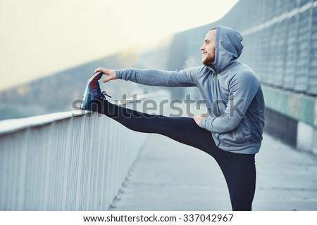Male runner doing stretching exercise, preparing for morning workout in the park