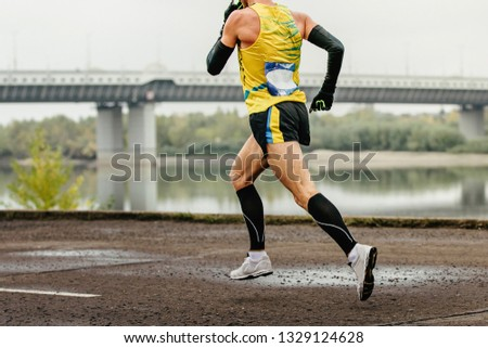 male runner in compression socks and protective arm sleeves run river embankment