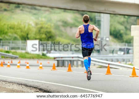 male runner in compression socks running in road with traffic cones safety #645776947