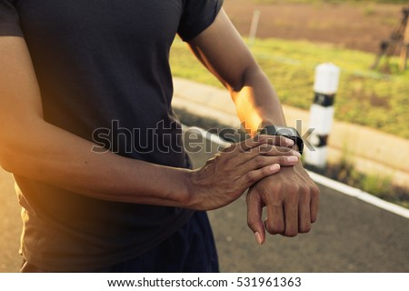 Male runner jogging outside looking at his wearable fitness tracker outside #531961363