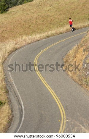 Male runner on winding rural road