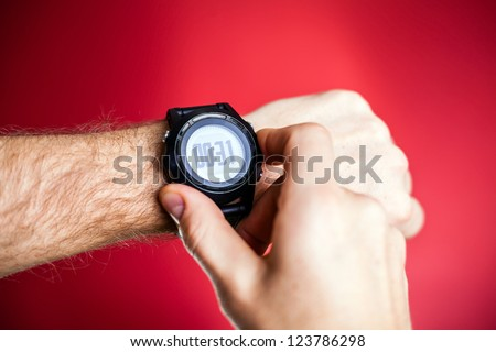 Male runner ready to run with sport watch smartwatch. Taking pulse trace or checking gps position wristwatch, using heart monitor. Man and fitness, exercising concept.