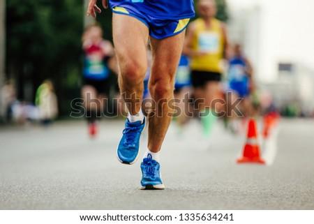 male runner run ahead of group runners urban marathon #1335634241