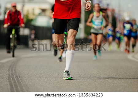 male runner running in front group runners on street of city #1335634223
