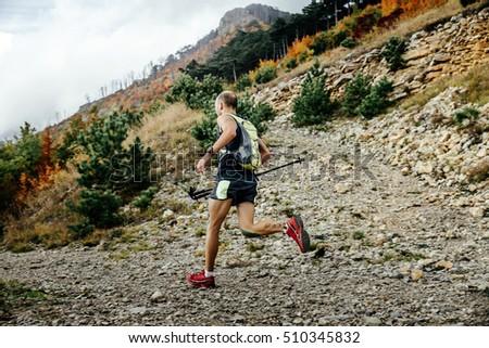 male runner running mountain marathon with nordic sticks during race in skyrunning #510345832