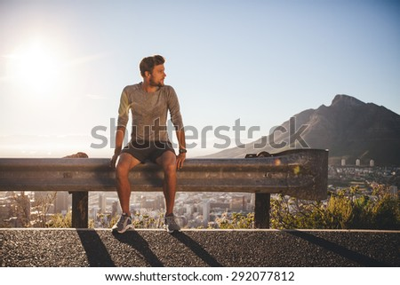 Male runner sitting on a guardrail on country road looking away on sunny day. Young man taking a break after morning run outdoors with bright sunlight.