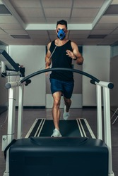 Male runner wearing mask on treadmill in sports science laboratory. Sports man running on treadmill and monitoring his fitness performance.