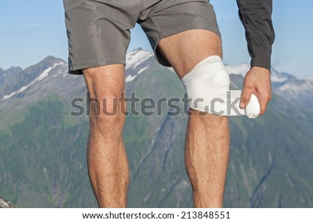 Male runner wearing shorts on top of mountain with beautiful scenic view wraps injured knee with white sports bandage