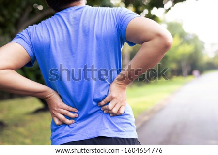 Male runners have a backache due to heavy fighting at the park.