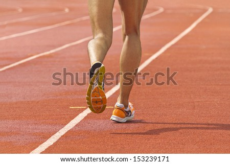 Male running at a track and field stadium