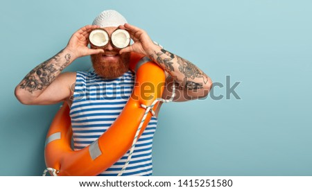 Male safeguard supervises situation on sea, holds two coconuts on eyes instead of binoculars, wears white swimhat, sailor vest, uses safety equimpent like ring buoy, poses over blue wall, blank space #1415251580