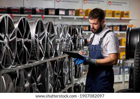 male salesman in auto shop making notes, checking the document and examining characteristics, looking at rack with auto rims
