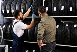 male salesman showing wheel tires to caucasian man customer at car repair service and auto store shop, they are discussing and talk about advantages of tires