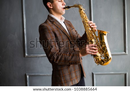 Male saxophonist plays jazz saxophone in a room on the background of a gray wall
