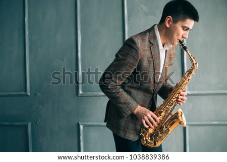 Male saxophonist plays jazz saxophone in the room