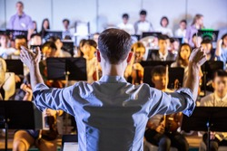 Male school conductor conductiong his student band to perform music in a school concert