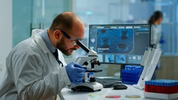 Male scientist looking under microscope in medical development laboratory, entering data in computer. Specialists working on medicine, biotechnology research in advanced pharma lab