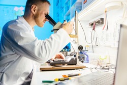Male scientist wearing robe uses microscope for examining and soldering components on electronic cirquit board.