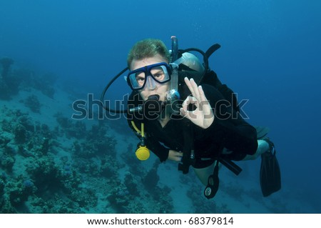 Male scuba diver gives OK sign in clear blue water #68379814