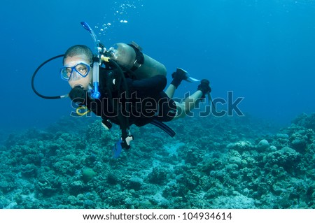 male scuba diver swims in the red sea on a coral reef
