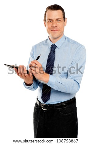 Male secretary taking down notes from boss on notepad looking at camera