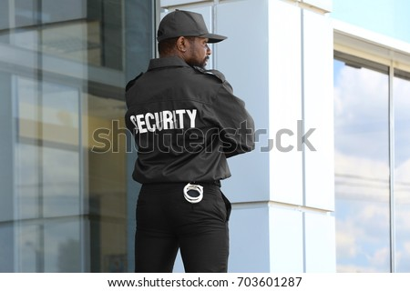 Male security guard standing near big modern building