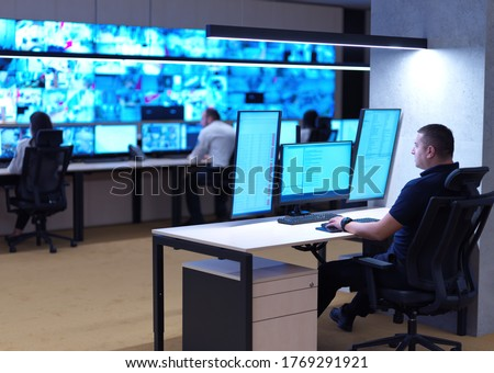 Photo of  Male security operator working in a data system control room offices Technical Operator Working at  workstation with multiple displays, security guard working on multiple monitors  Male computer opera