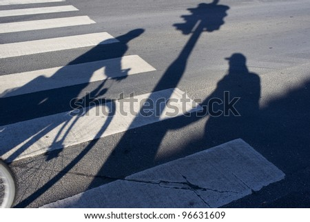 Male senior pedestrian waiting for green light by an urban zebra crossing while a cyclist hurry by.