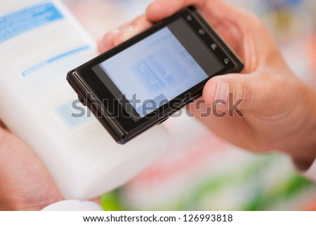 Male shopper clicking photograph of product's information at supermarket
