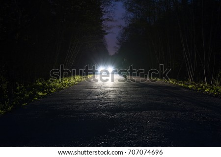Male silhouette at the edge of a dark mountain road through the forest in the night. Man standing on the road against the car headlights. The car on the roadside. Mystery concept. Soft focus, filter. #707074696