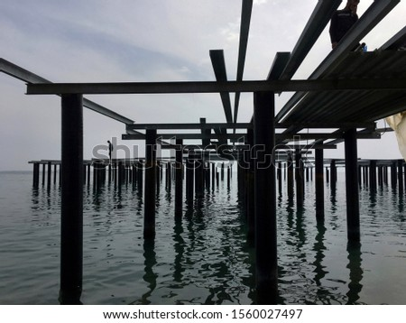 Male silhouette on pier construction structures in the water #1560027497