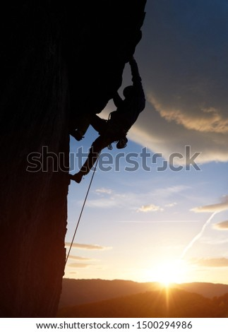 Male silhouette rock climbing, doing next step at sunrise in mountains. Rock climber hanging on cliff above glowing horizon under big clouds. Side view. Dangerous, extreme, endurance, victory concept