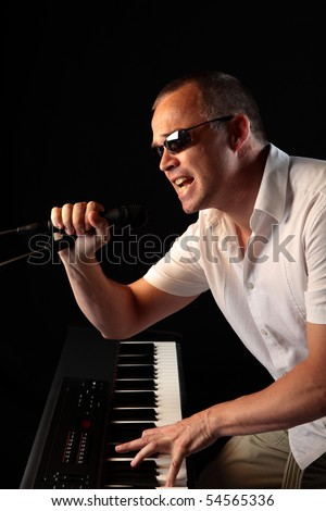 Male Singer Playing Keyboard While Holding Microphone On ...