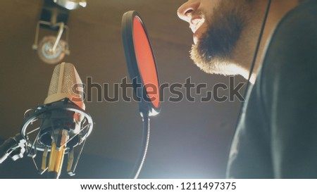 Male singer singing in sound studio. Man recording new song. Guy with beard sings to microphone. Working of creative musician. Show business concept. Bottom view Slow motion Close up. #1211497375