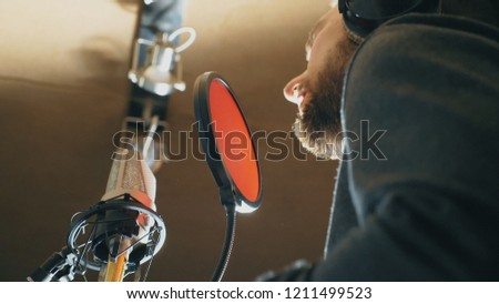 Male singer singing in sound studio. Man recording new song. Guy with beard sings to microphone. Working of creative musician. Show business concept. Bottom view Slow motion Close up #1211499523