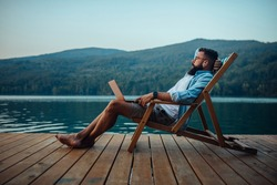 Male sitting on cozy chair near lake and using laptop while holding it in his lap.