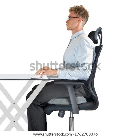 Male sitting on office chair at desk with good posture and support ストックフォト ©