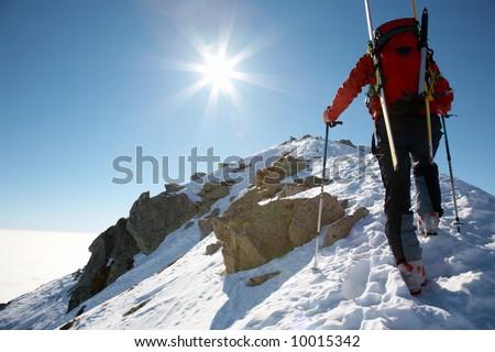 Male ski-climber climbing a snowy ridge; horizontal frame. Italian alps.