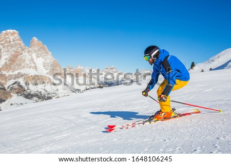 Male skier in blue and yellow clothes on slope with mountains in the background at Cortina d'Ampezzo Faloria skiing resort area Dolomiti Italy Foto stock ©