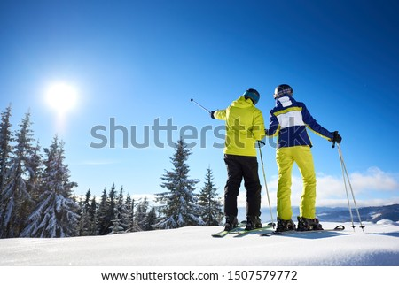 Male skier showing with ski poles on sun high in blue sky over winter mountains. Back view of couple resting during skiing on sunny winter day. Picturesque view of nature in mountains. Copy space. #1507579772