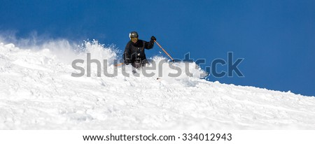 Male skier skiing off piste in powder snow a sunny winter day. #334012943