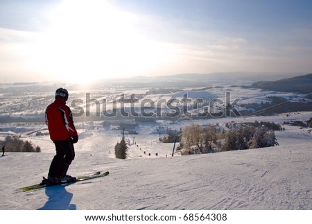 Male skier standing on slope. Winter mountain landscape. Bright sunlight.
